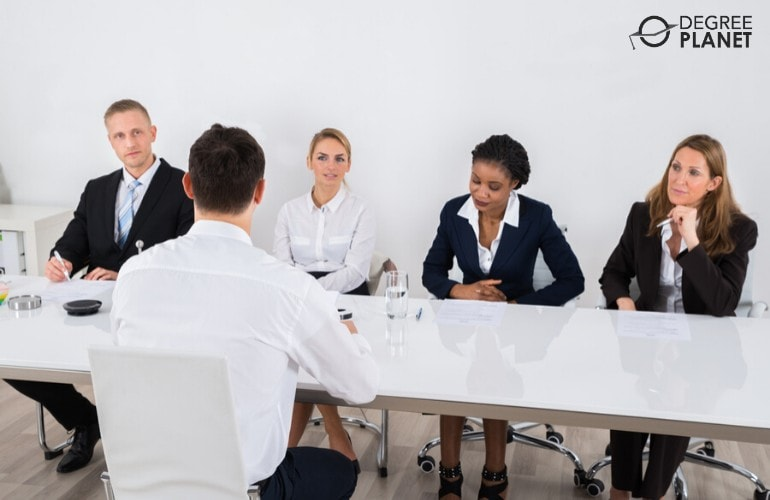student in front of interviewers during admissions interview
