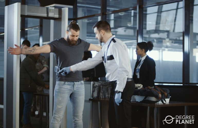 airport security guard checking passengers in airport