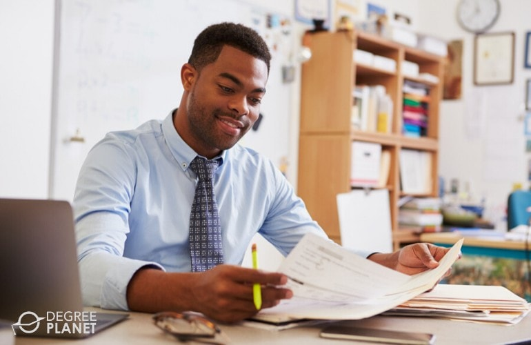 teacher reviewing documents in his office