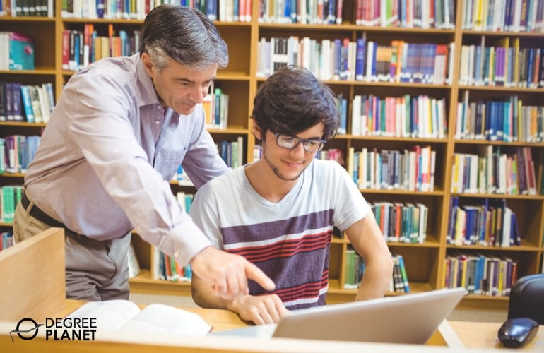 college professor helping his student in the library