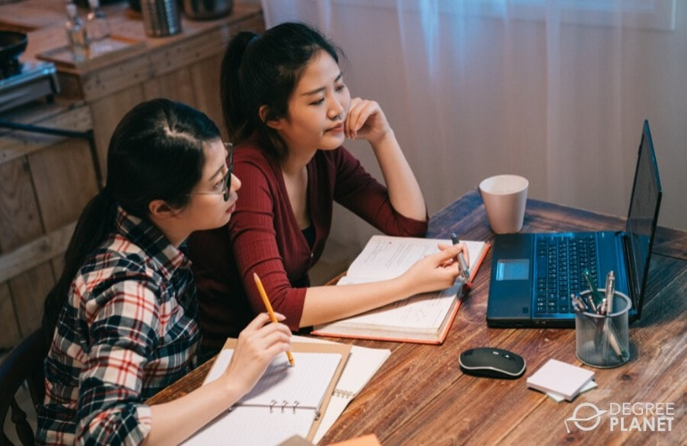 students studying together on laptop at home