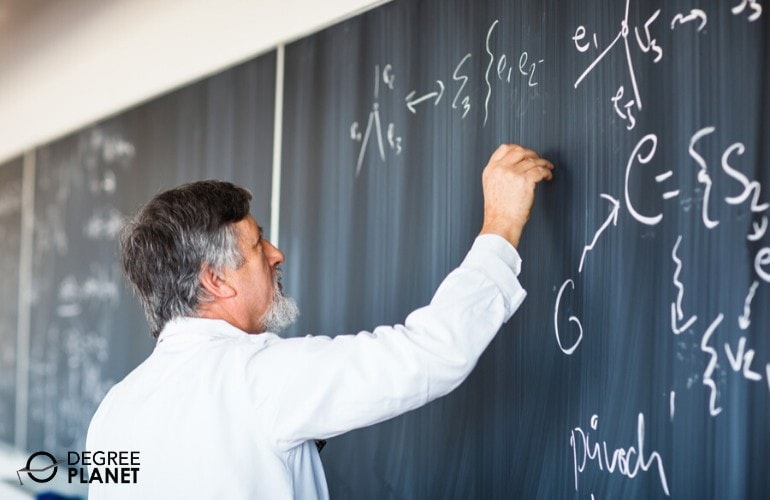 college professor writing on chalkboard