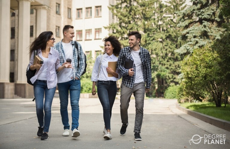 undergraduate students carrying textbooks across campus