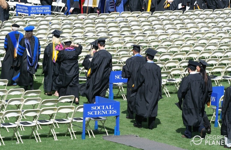 students walking to stage in a graduation ceremony