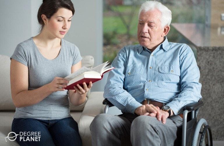 social worker reading a book to an elderly man