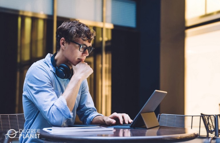 Bachelor's Degree student studying on his laptop