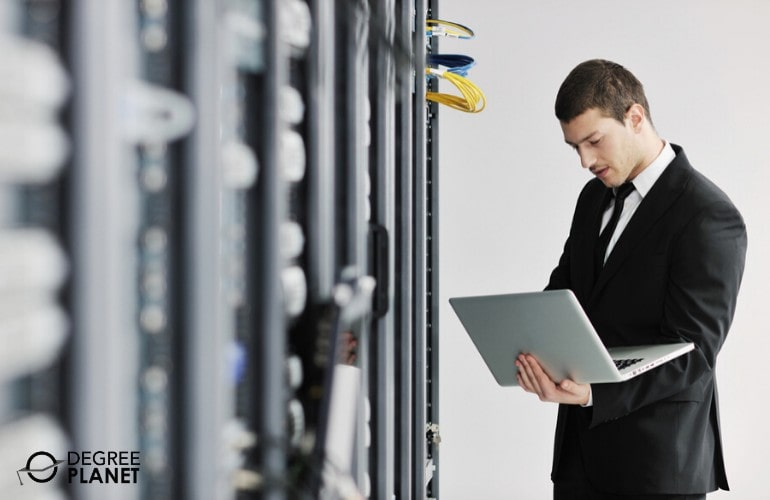 cyber security manager working on laptop in data center