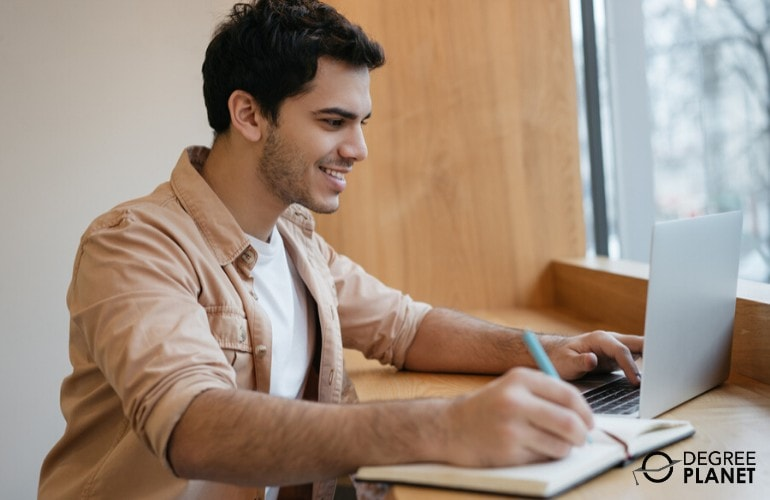 cyber security degree student studying on his laptop