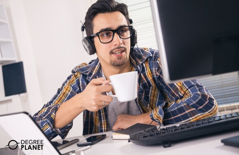 software developer drinking coffee while working in his office