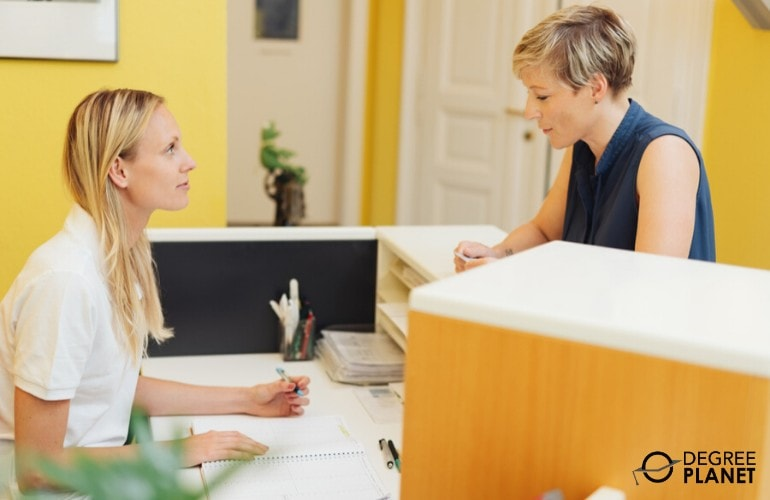 clinic receptionist speaking to a client