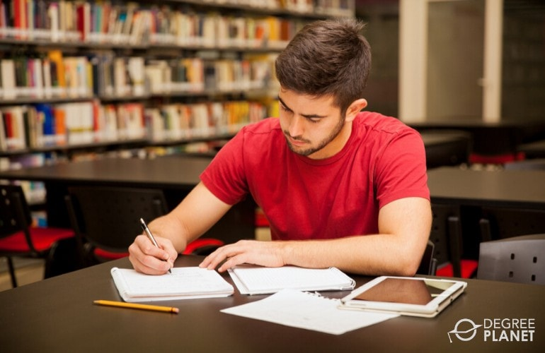 associates degree student studying at the library