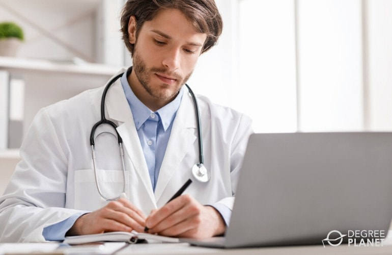 healthcare administration student studying on his laptop