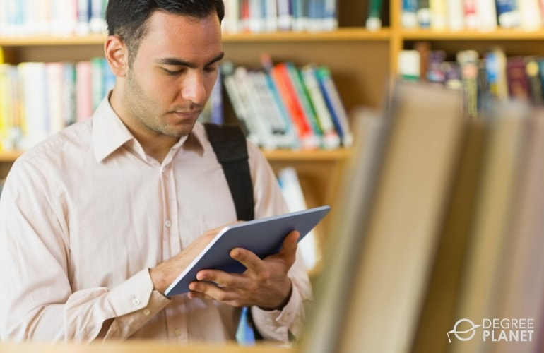 college student searching for a book in the library