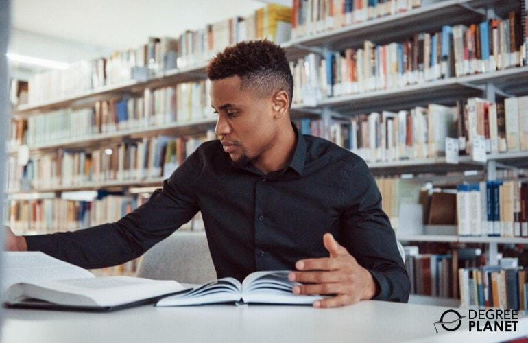 graduate degree student studying in a library