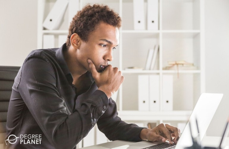 Information Security Analyst thinking in front of his laptop