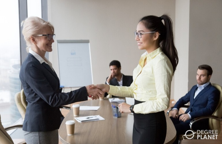 Human Resources Director congratulating an employee during a meeting
