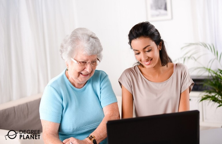 social worker helping a senior woman use the laptop