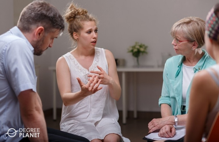 substance abuse counselor listening to her patients during group counselling