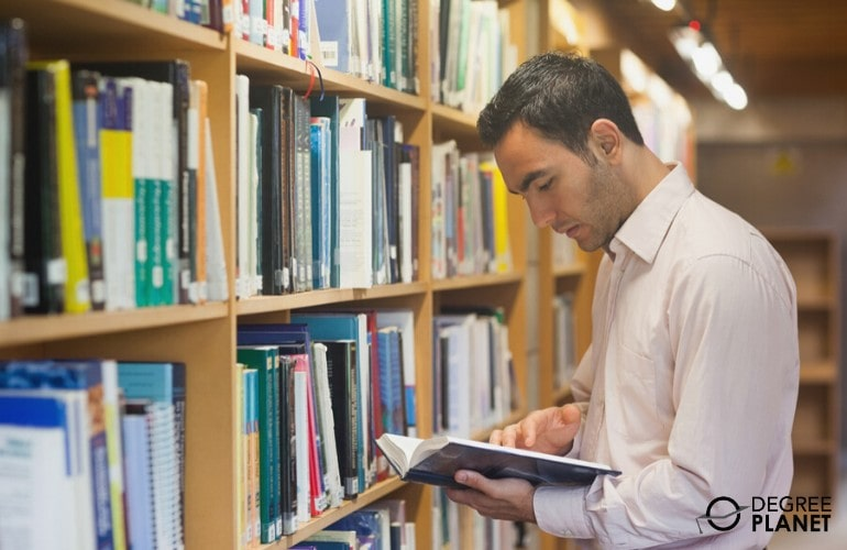 PhD in Human Services student searching for a book in the library