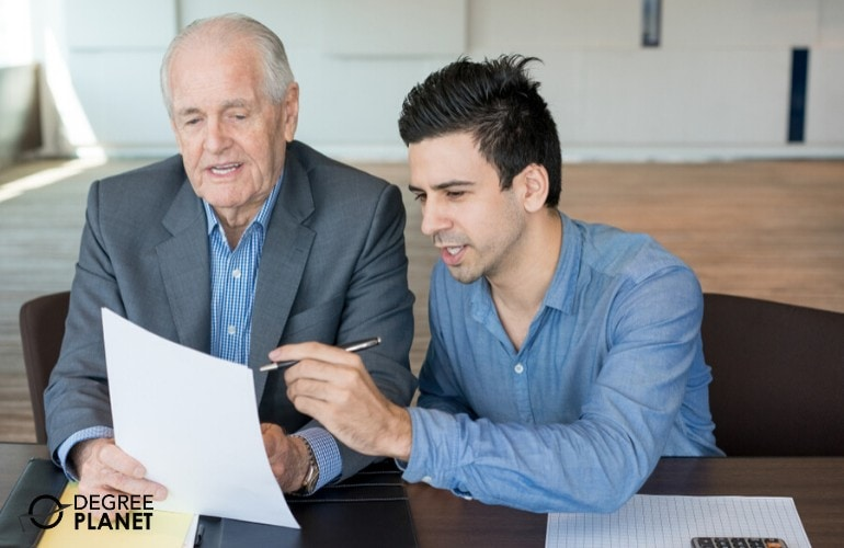 Senior Financial Analyst working with fellow analyst in the office