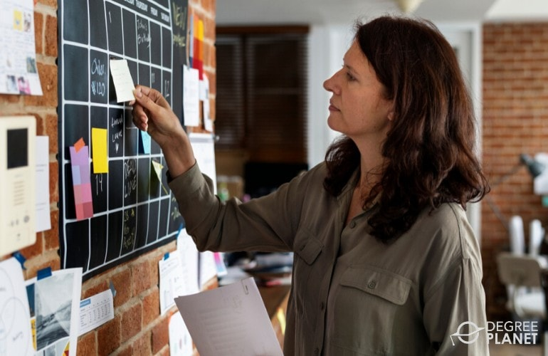 Event Planner getting a sticky note from announcement board