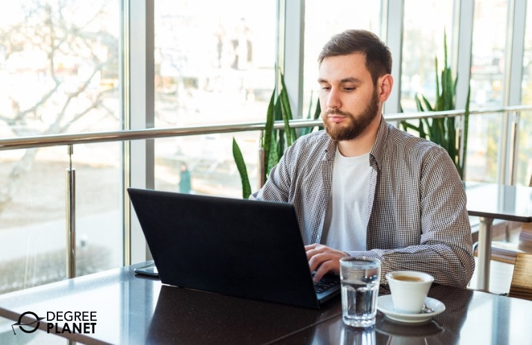 Doctorate in Information Technology student studying at a cafe