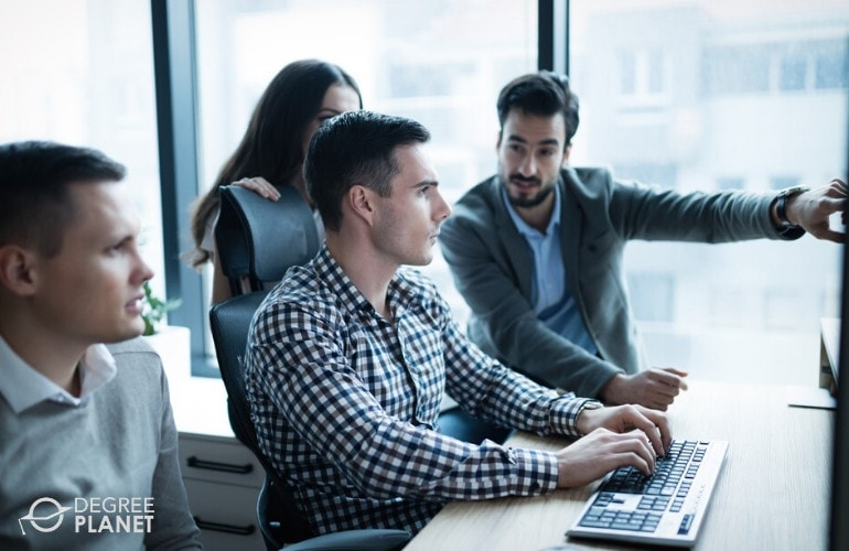 Information Security Analysts working on a project together