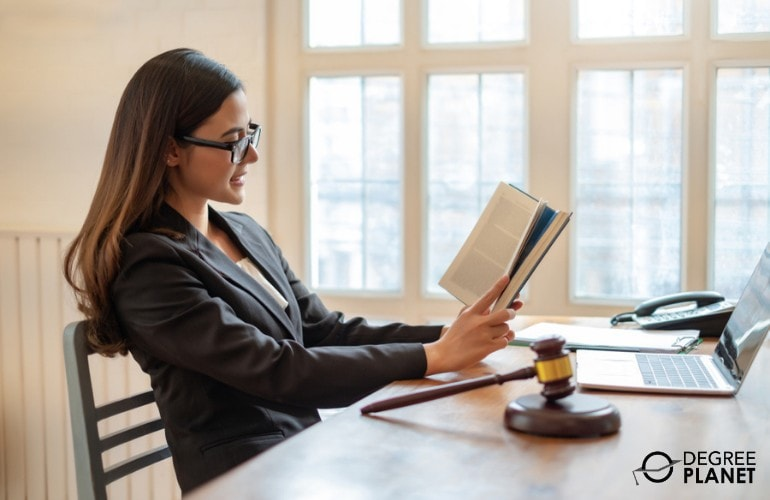 Female lawyer reading a book in her office