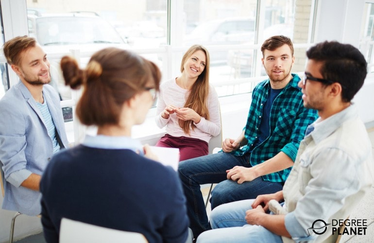 Psychologist with a group of people during group therapy