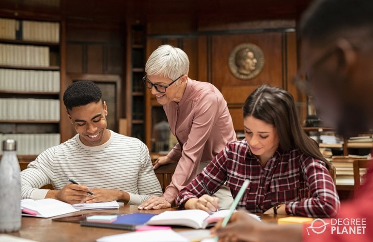 College Professor assisting her students in library