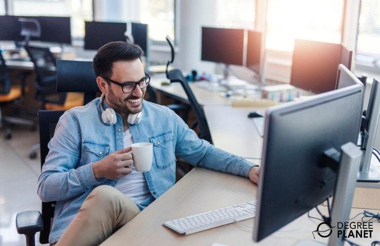 Software Developer enjoying his coffee while working