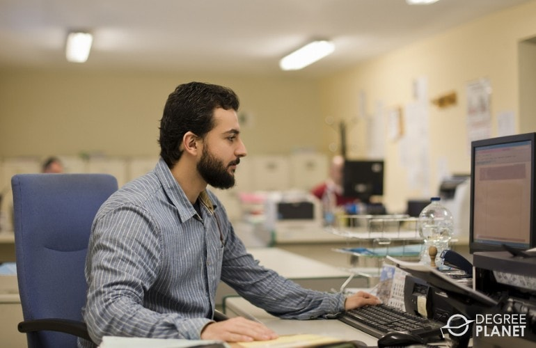 Payroll Clerk working on his table in an office