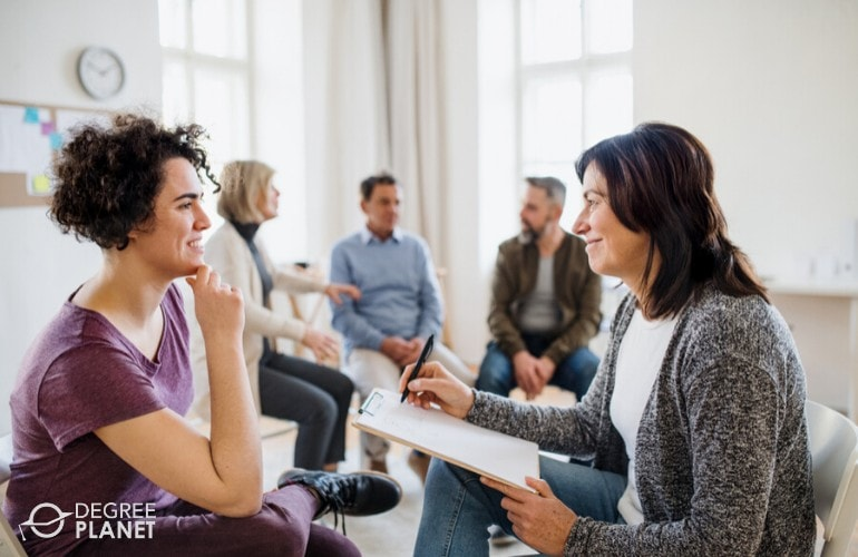 Behavioral Disorder Counselor talking to a patient during group therapy