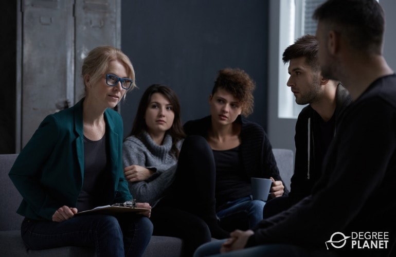 addiction therapist talking to patients during group therapy