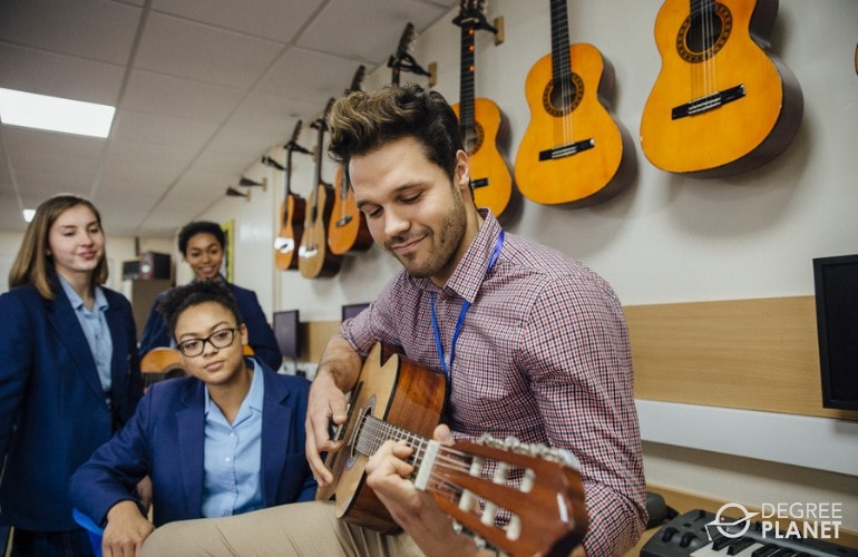 Music teacher teaching his students how to play guitar